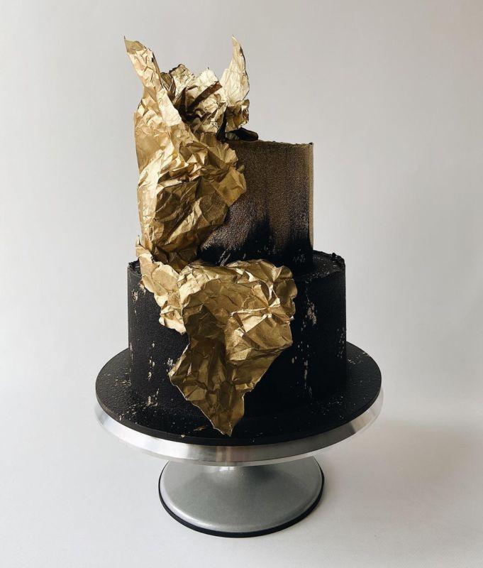 Черный двухэтажный торт украшен рисовой бумагой покрытой золотым цветом.