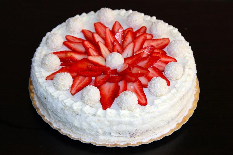 Торт Рафаэлло оформлен свежей клубникой и конфетами